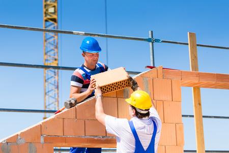 Photo pour Two Bricklayer or builder or worker build or bricklaying or laying a stone or brick wall on construction or building site - image libre de droit