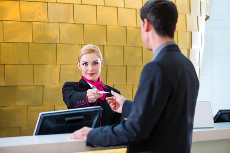 Photo for Man in Hotel check in at reception or front office being given key card - Royalty Free Image
