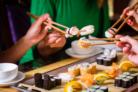 Photo pour Young people eating sushi in Asian restaurant - image libre de droit