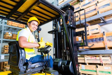 Photo pour Asian fork lift truck driver lifting pallet in storage warehouse - image libre de droit