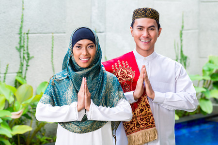 Photo for Asian Muslim man and woman welcoming guests wearing traditional dress - Royalty Free Image