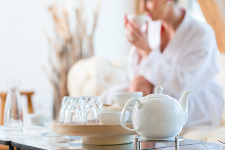 Photo for Woman in bath robe drinking tea in wellness spa relaxation room - Royalty Free Image