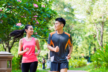 Photo for Asian Chinese man and woman jogging in city park - Royalty Free Image
