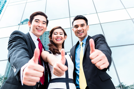 Asian business woman and men outside in front of building