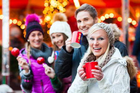 Photo pour Friends drinking mulled wine and eating crystalized appels on German Christmas Market - image libre de droit