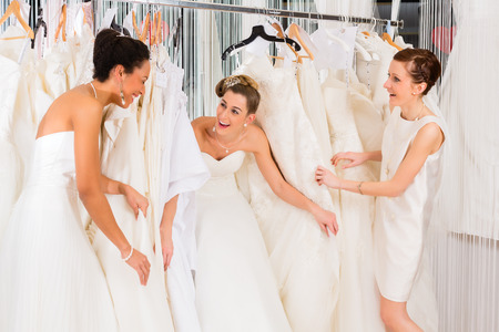 Photo for Women having fun during bridal gown fitting in wedding fashion store - Royalty Free Image