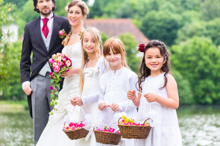 Photo pour Wedding couple bride and groom with flower children or bridesmaid in white dress and flower baskets - image libre de droit