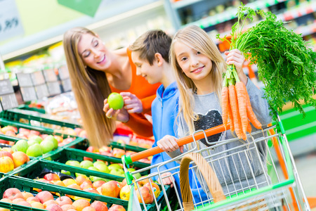 Photo pour Family selecting fruits and vegetables while grocery shopping in supermarket - image libre de droit