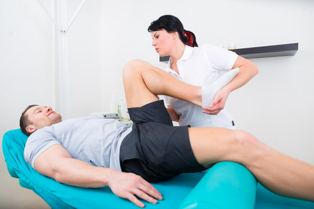 Foto de Patient at the physiotherapy doing physical exercises with his therapist - Imagen libre de derechos