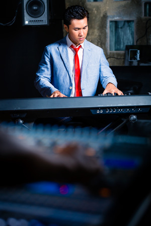 Asian professional pianist playing keyboard in recording studio