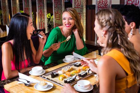Photo pour Young people eating sushi in Asian restaurant - image libre de droit