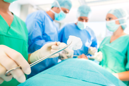 Foto de Hospital - surgery team in the operating room or Op of a clinic operating on a patient, perhaps it's an emergency a assistant holding a cotton swap forceps - Imagen libre de derechos