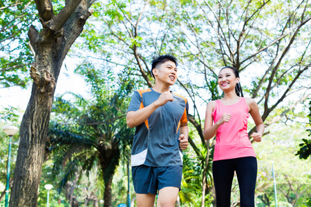 Foto de Asian Chinese man and woman jogging in city park - Imagen libre de derechos