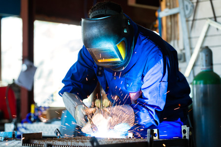Photo for Welder bonding metal with welding device in workshop, lots of sparks to be seen, he wears welding googles - Royalty Free Image