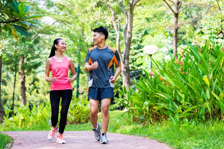 Photo pour Asian Chinese man and woman jogging in city park - image libre de droit