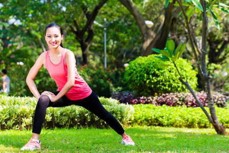 Photo for Asian Chinese woman stretching muscles for fitness in city park - Royalty Free Image
