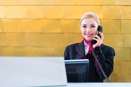 Photo for Hotel receptionist with phone on front desk - Royalty Free Image