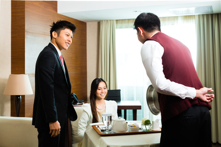Photo for Asian Chinese room service waiter or steward serving guests food in a grand or luxury hotel room - Royalty Free Image