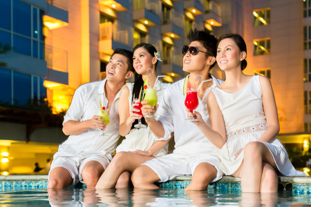 Foto per Two young and handsome Asian Chinese couples or friends drinking cocktails in a luxurious and fancy hotel pool bar - Immagine Royalty Free