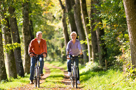 Foto de Senior Man and woman exercising with bicycles outdoors, they are a couple - Imagen libre de derechos
