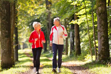 Photo pour Senior Couple doing sport outdoors, jogging on a forest road in the autumn - image libre de droit