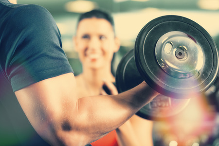 Photo for Man or Bodybuilder with his personal fitness trainer in the gym exercising sport with dumbbells, closeup - Royalty Free Image