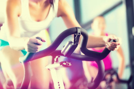Foto per Young People - group of women and men - doing sport Spinning in the gym for fitness - Immagine Royalty Free
