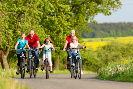 Foto de Family with three girls having a weekend excursion on their bikes or bicycles on a summer day in beautiful landscape - Imagen libre de derechos