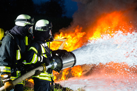Foto de Firefighter - Firemen extinguishing a large blaze, they are standing with protective wear in front of wall of fire - Imagen libre de derechos