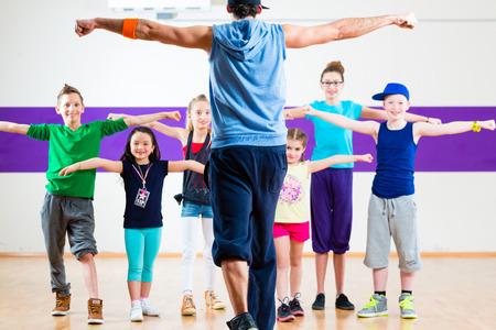 Foto de Dance teacher giving children fitness class in gym - Imagen libre de derechos