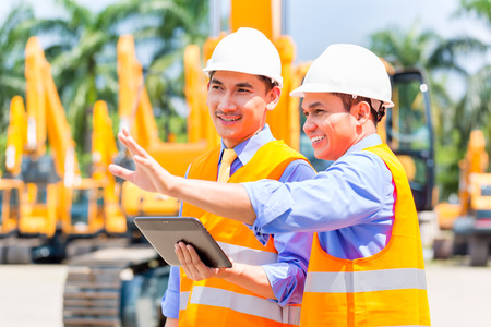 Photo pour Asian engineer controlling construction machinery of construction site or mining company - image libre de droit