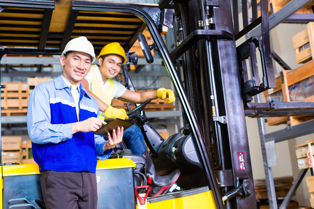 Photo pour Asian fork lift truck driver discussing checklist with foreman in warehouse - image libre de droit