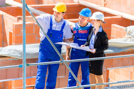 Photo pour Construction site Team or architect and builder or worker with helmets discuss on a scaffold construction plan or blueprint or checklist - image libre de droit