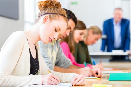 Foto de University college students writing test or exam - Imagen libre de derechos