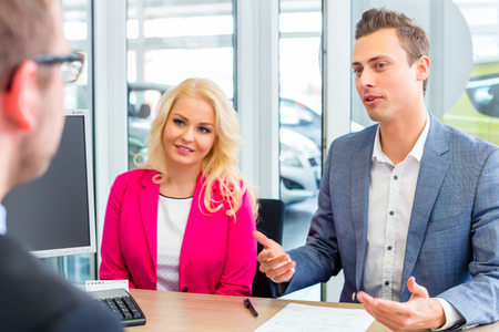 Photo for Couple buying car at dealership and negotiating price with salesman - Royalty Free Image