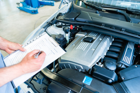 Foto per Auto mechanic controlling  car with checklist in workshop - Immagine Royalty Free