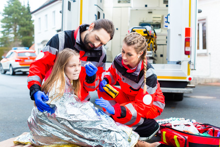 Foto de Emergency doctor and paramedic or ambulance team helping accident victim - Imagen libre de derechos