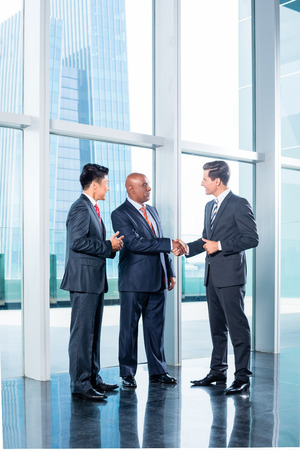 Photo for Diversity business team concluding contract with handshake in front of city skyline - Royalty Free Image