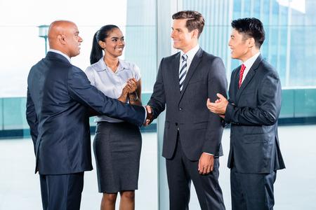 Foto de Diversity business team concluding contract with handshake in front of city skyline - Imagen libre de derechos