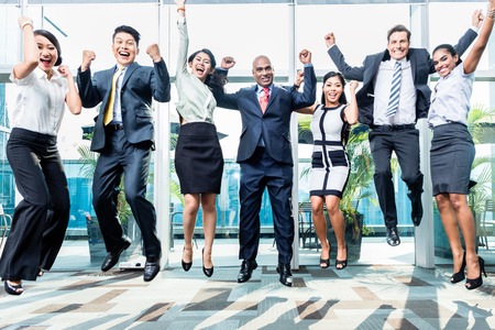Photo pour Diversity business team jumping celebrating success, Chinese, Indonesian, Indian, and Caucasian ethnicities - image libre de droit