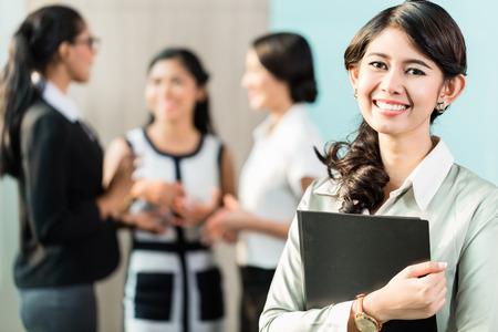 Foto de Indonesian Business woman standing in front of team - Imagen libre de derechos