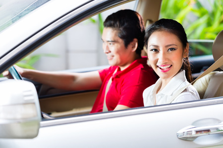 Photo pour Asian couple driving new car on driveway to their home - image libre de droit