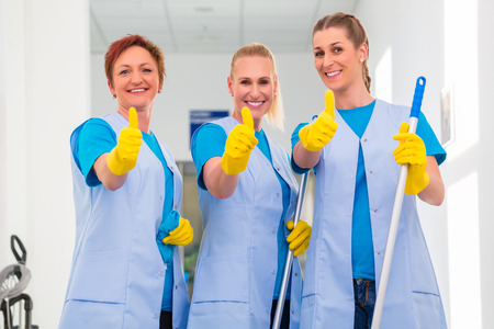 Foto de Cleaning ladies working in team showing the thumbs up sign - Imagen libre de derechos