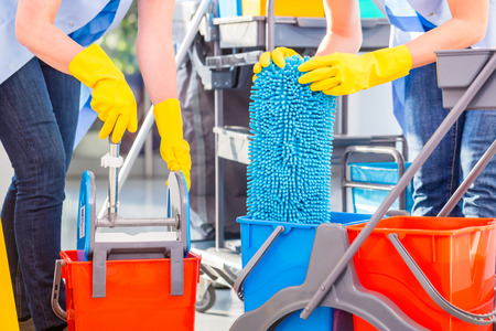 Photo pour Cleaning ladies mopping floor, close up on hands and tools - image libre de droit