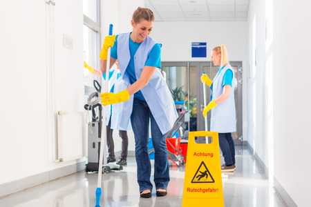 Photo pour Commercial cleaning brigade working mopping the floor - image libre de droit