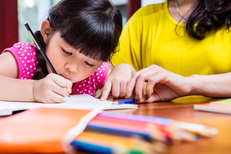 Photo for Chinese mother homeschooling her child teaching her daughter to write - Royalty Free Image