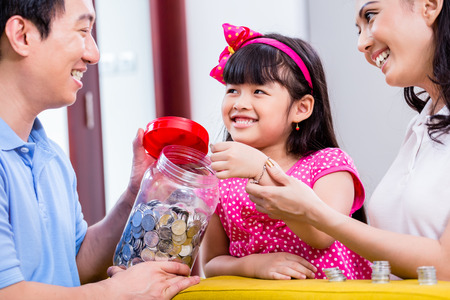 Foto de Chinese family saving money for college fund of child, putting coins in jar - Imagen libre de derechos