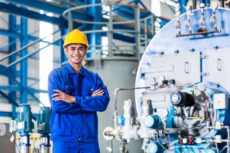 Foto de Proud Asian worker standing in production factory - Imagen libre de derechos
