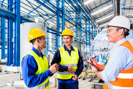 Photo pour Asian factory worker and engineer as team inspecting a machine delivery - image libre de droit