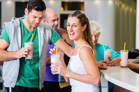 Photo for People drinking protein shakes in fitness gym bar - Royalty Free Image